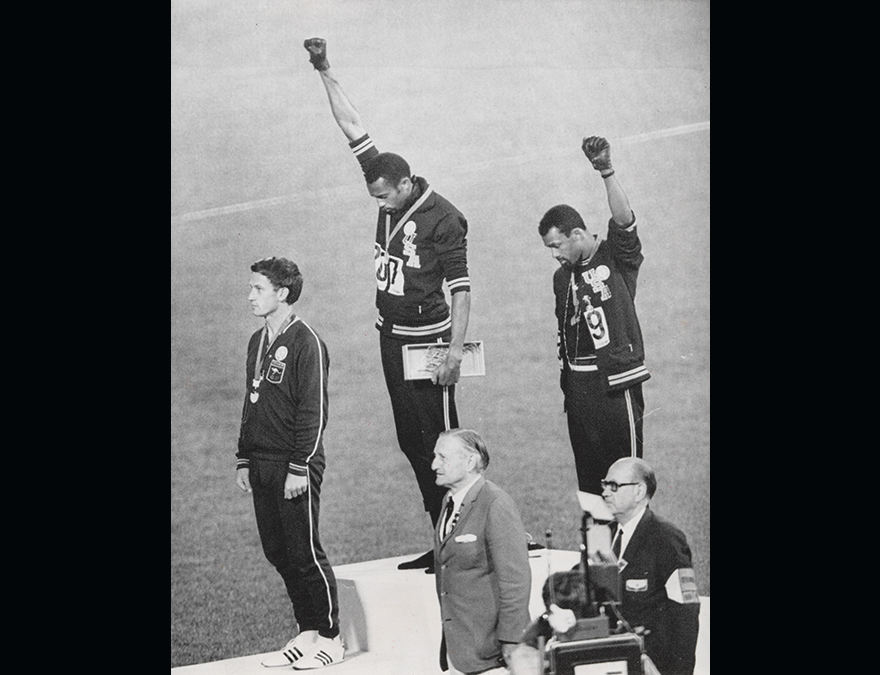 Three Olympic athletes two with their arms in the air