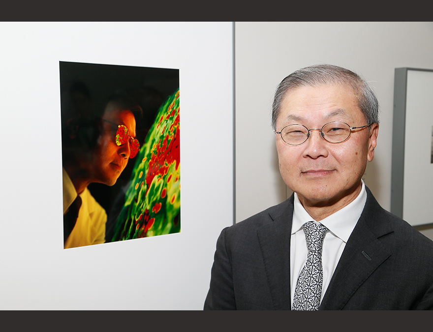Asian American man standing next to his portrait