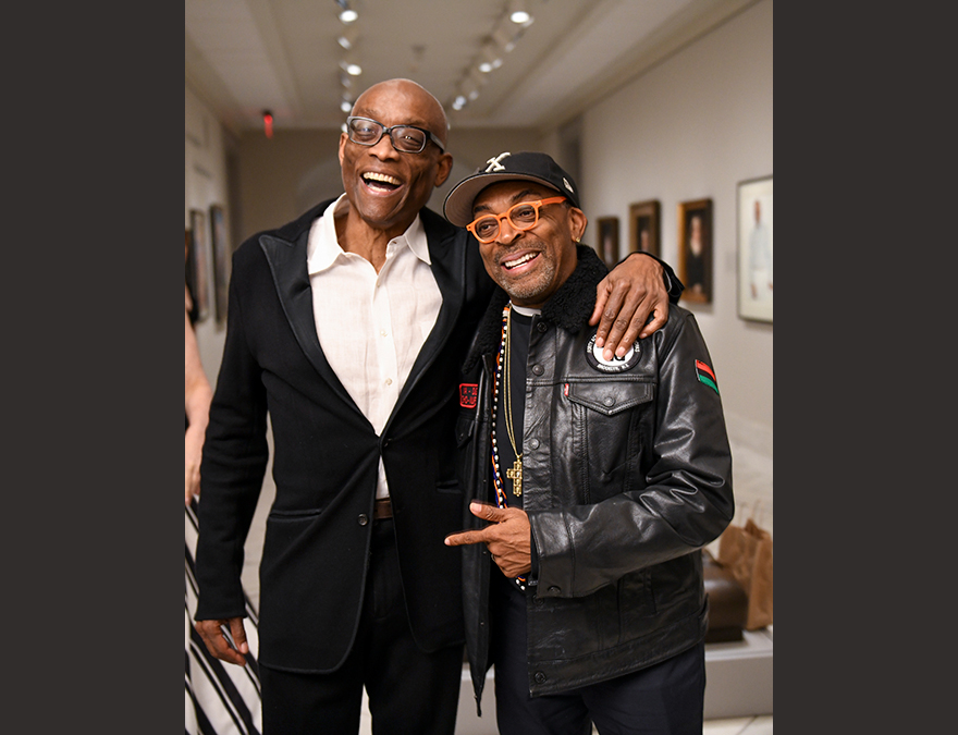 Two African American men--one in formalwear and the other  in a leather jacket and hat