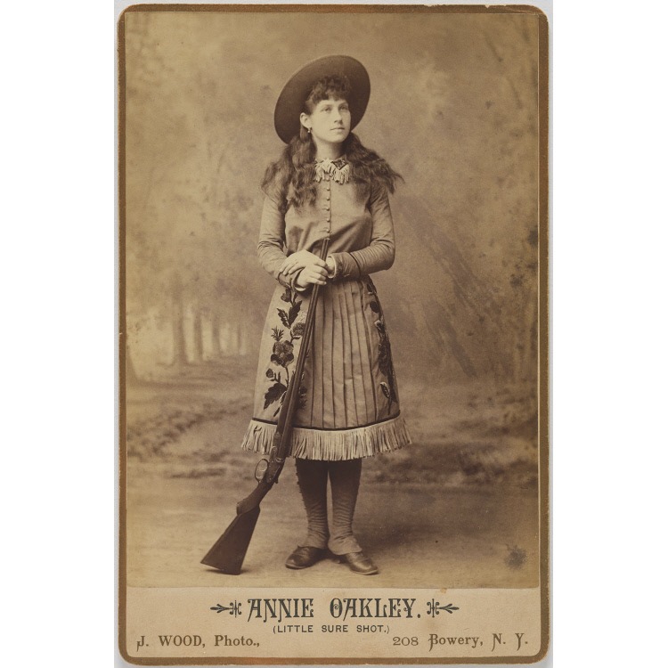 Photograph of a woman in western garb with a gun leaning against her leg