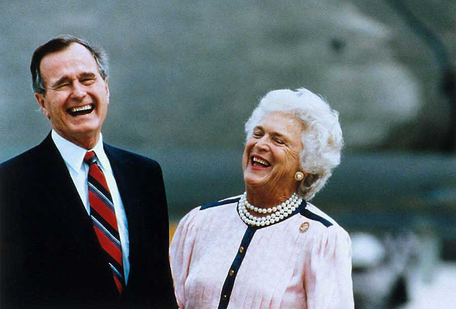 Color photograph of a man in a tie and a woman in a pink shirt laughing