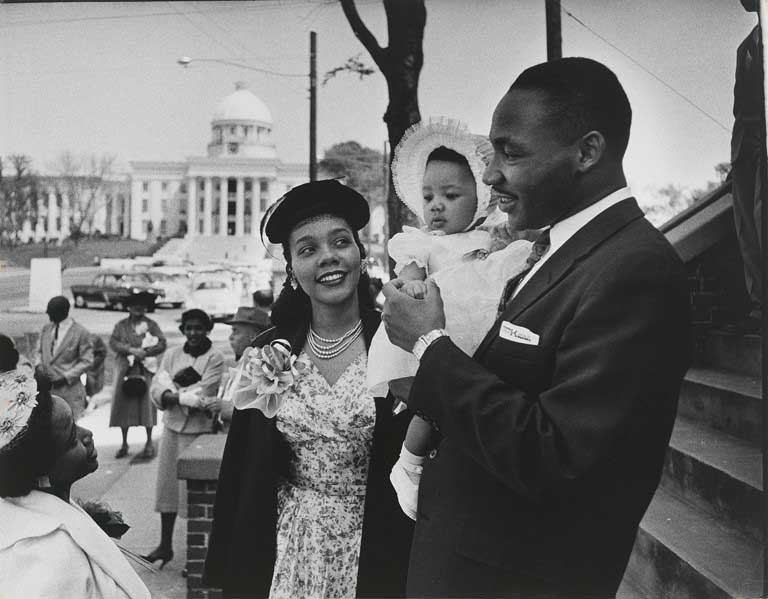 Black and white image of a man holding a baby in a bonnet and a woman looking up at them