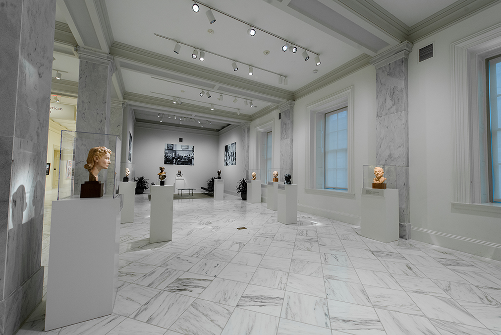 View of the exhibition, wide angle, many busts in room with white tiles and white walls