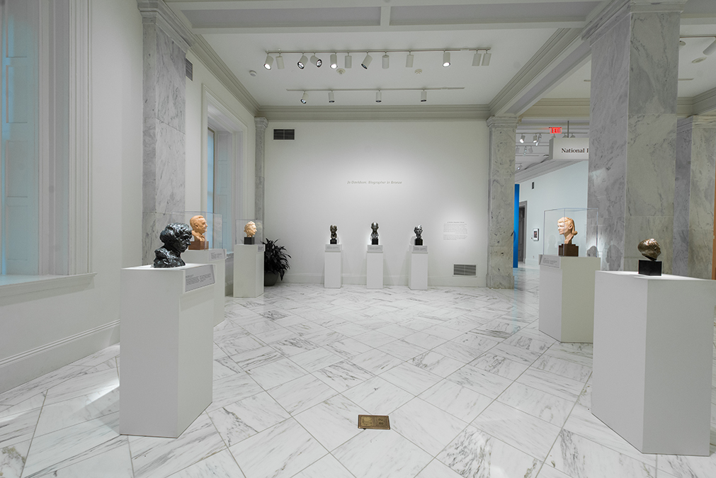 View of the exhibition, many busts in room with white tiles and white walls