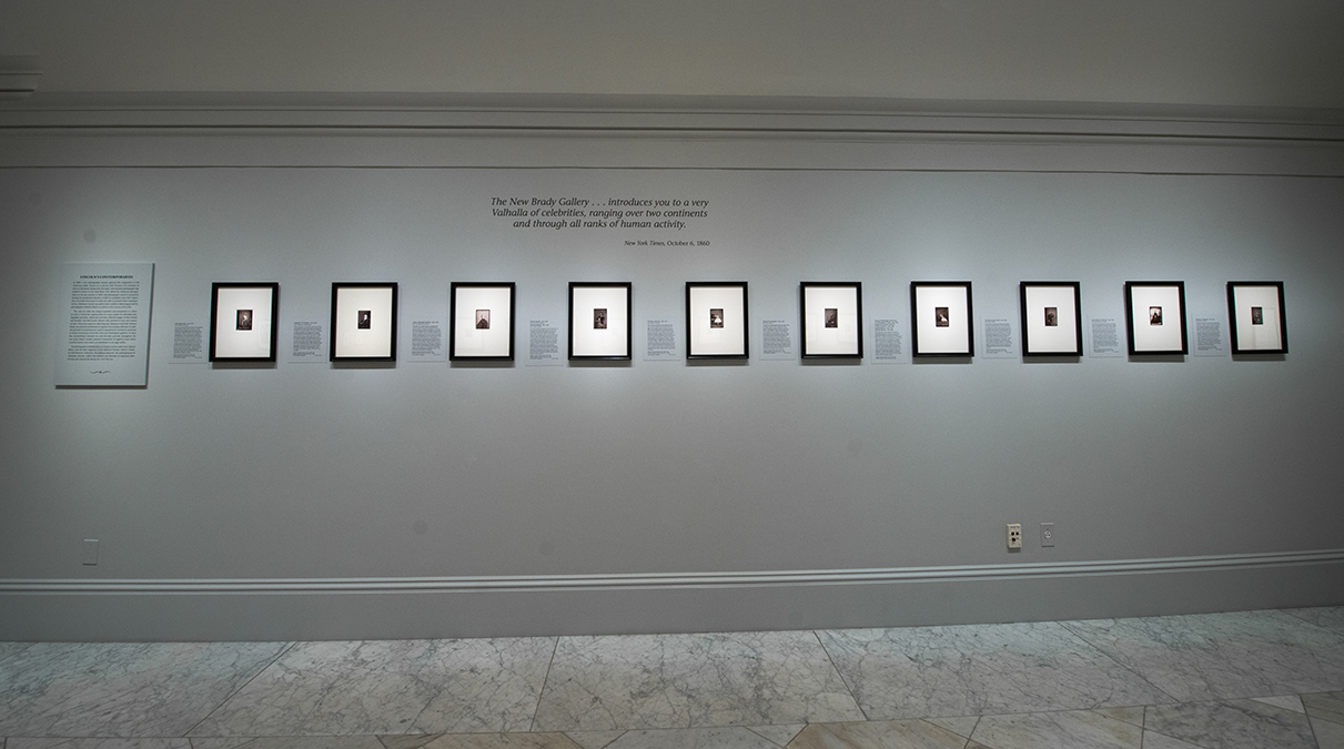 View of the exhibition, portraits on the wall, framed in the same size frames and uniformly spaced