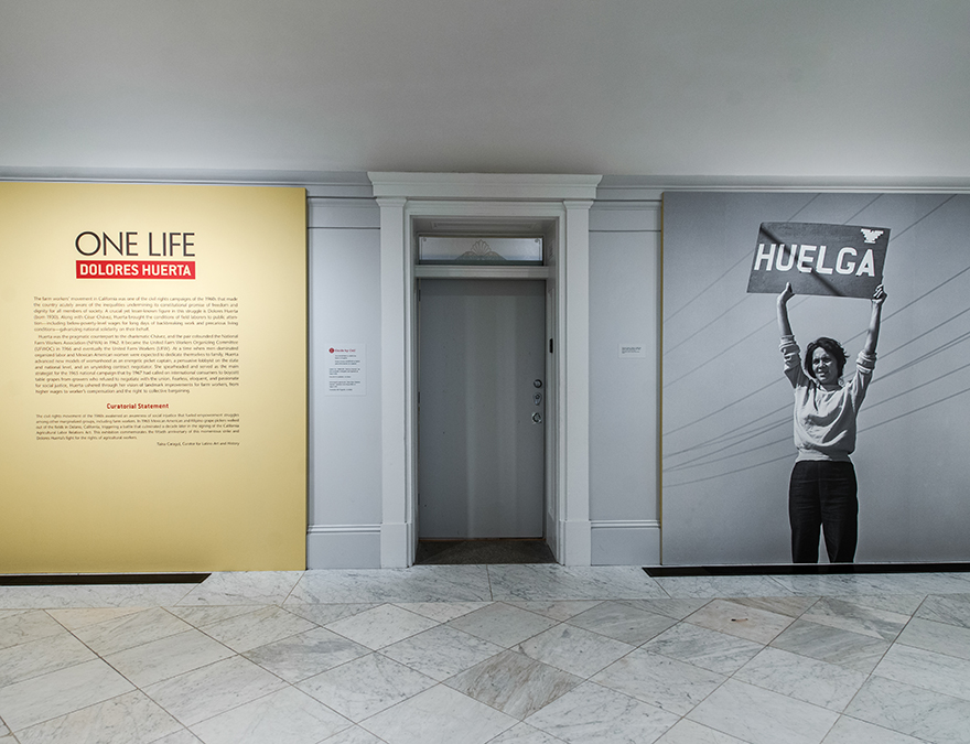 Photo of the Dolores Huerta exhibition entrance with an enlarged photo of her holding a protest sign plus wall text