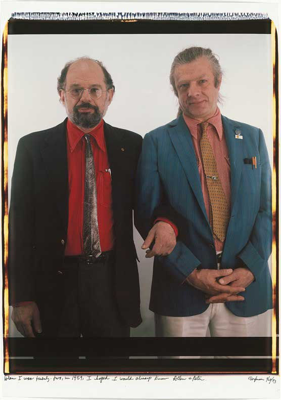 Two men in colorful shirts, ties and jackets standing arm-in-arm