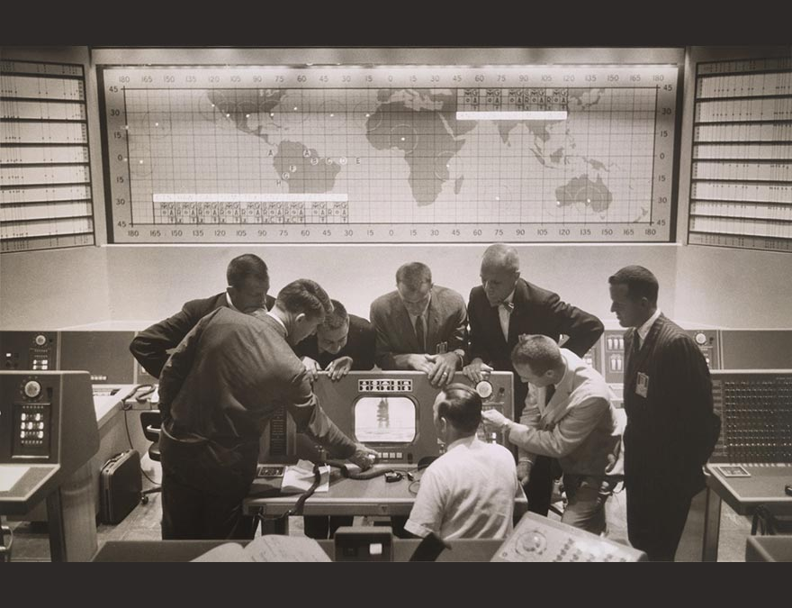 Group portrait of eight young to middle-aged men gathered around a console at the Cape Canaveral control center.