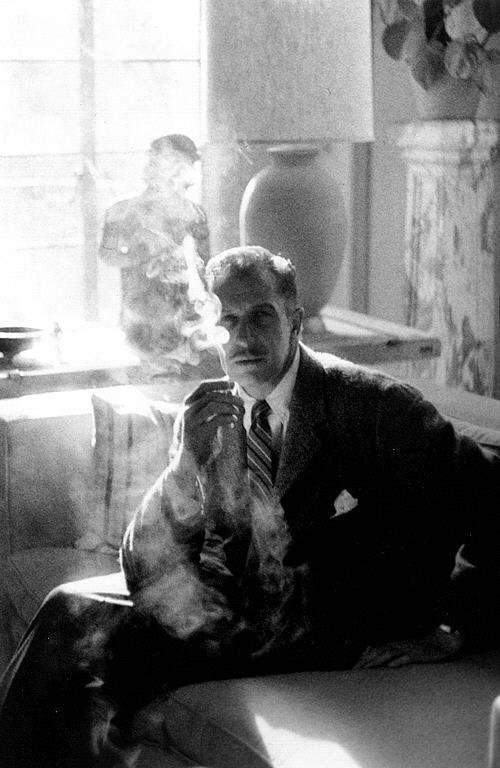 Photograph of a man seated and smoking a cigarette