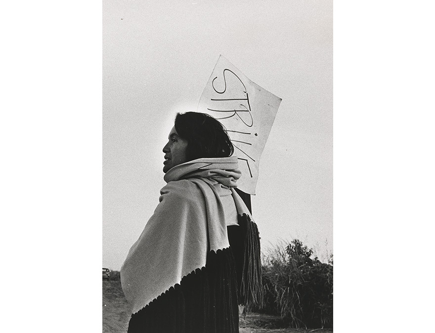 Dolores Huerta carrying a protest sign and draped in a blanket.