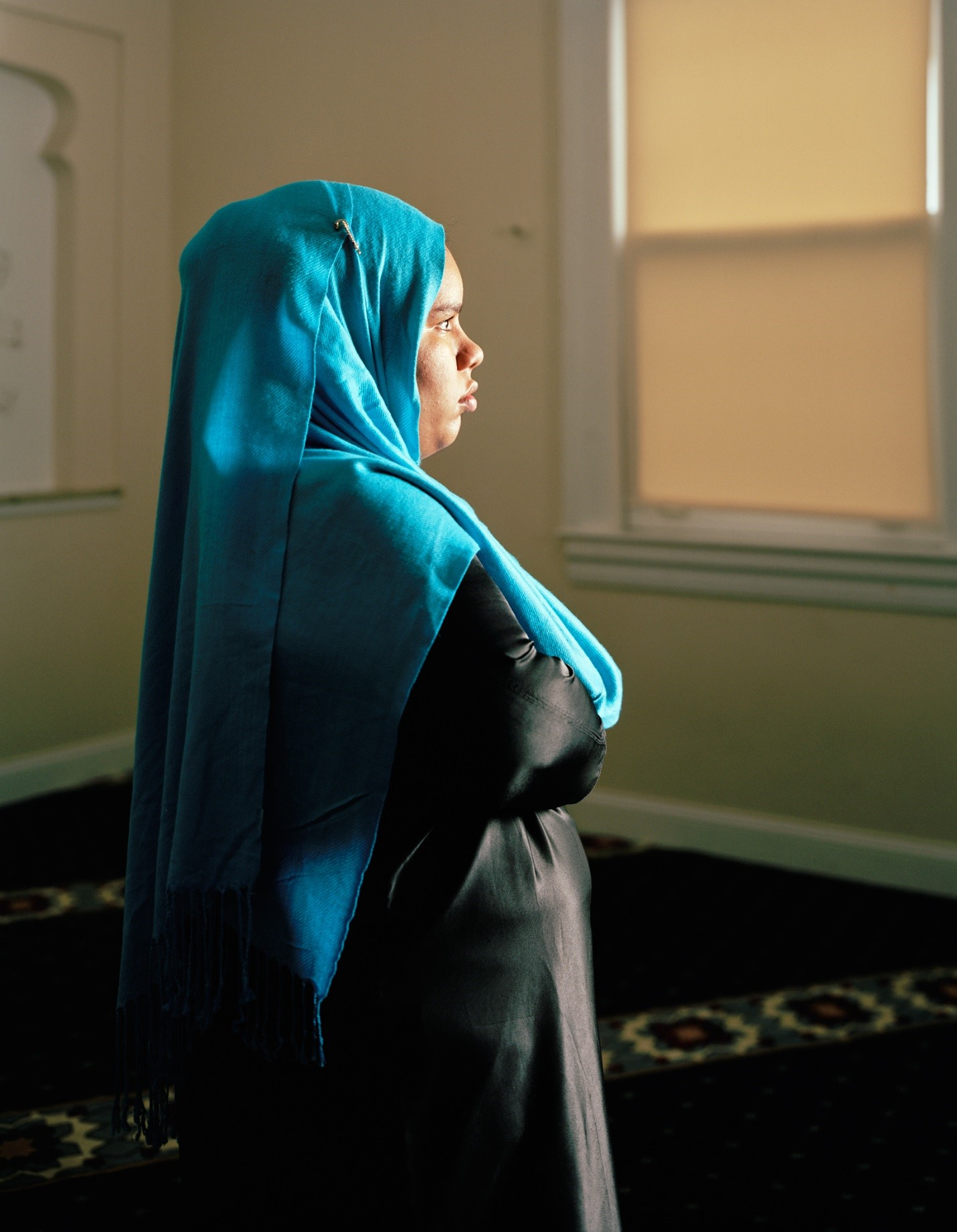 Woman in blue head scarf looking towards window