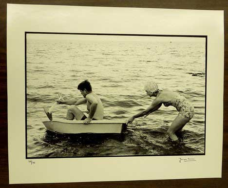 Black and white photograph of a woman pushing a man in a rowboat