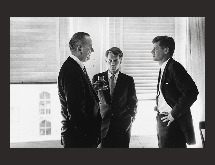 Three men in dark suits talking in a bright room
