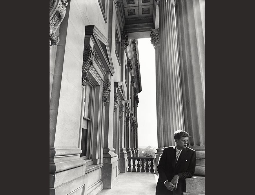 Black and white photo of John Kennedy leaning against a column at the Capitol