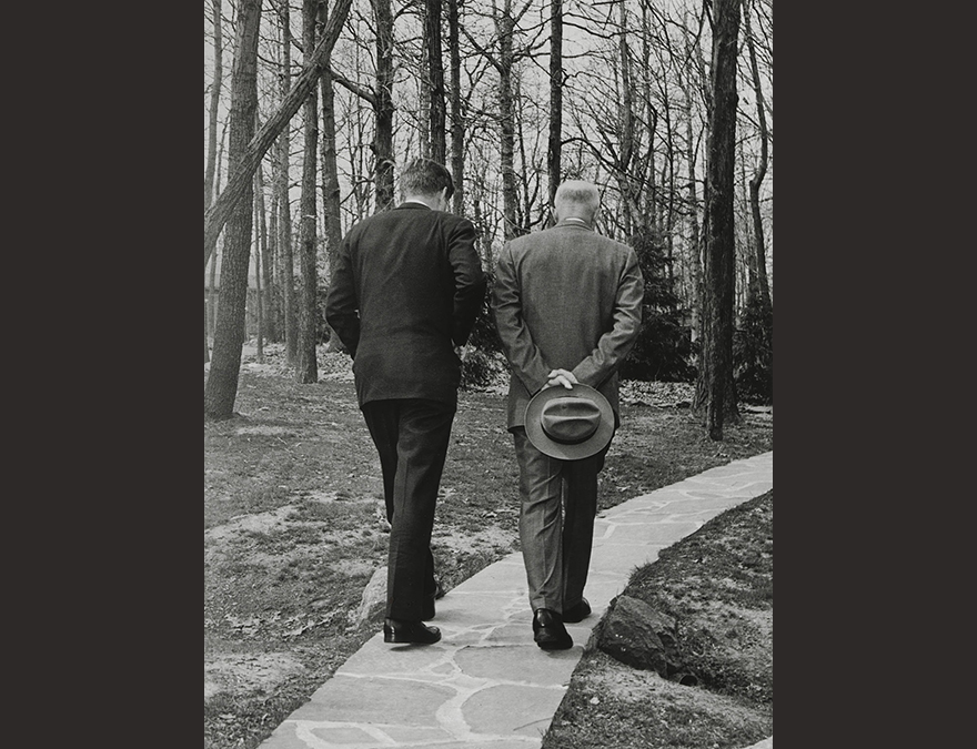 Two men one young and one older walking in the woods.  Their backs are to the camera