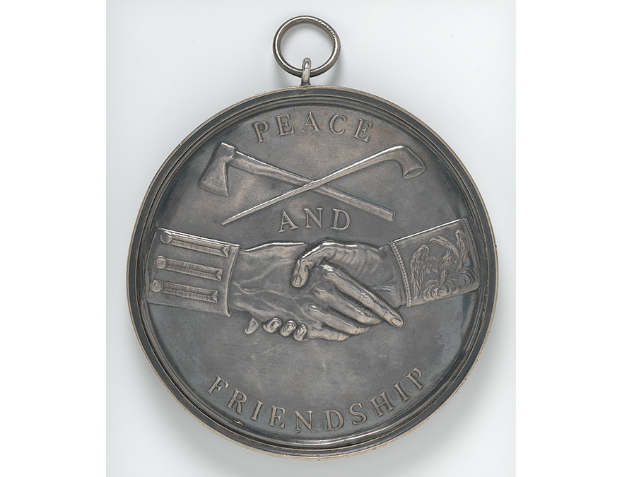 Peace medal featuring two hands grasped in a handshake