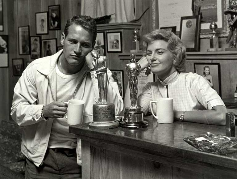 Black and white image of a man and woman leaning on a soda counter and drinking coffee