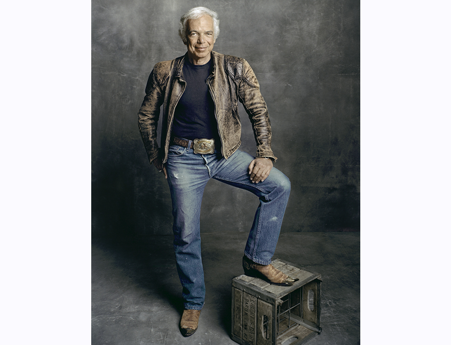 Gray-haried man in a leather jacket and jeans with one foot (in cowboy boots) on a wooden crate