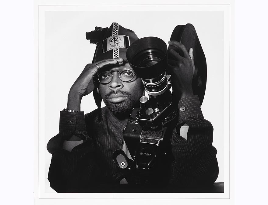 Young African American man with large glasses holding a movie camera and shading his eyes