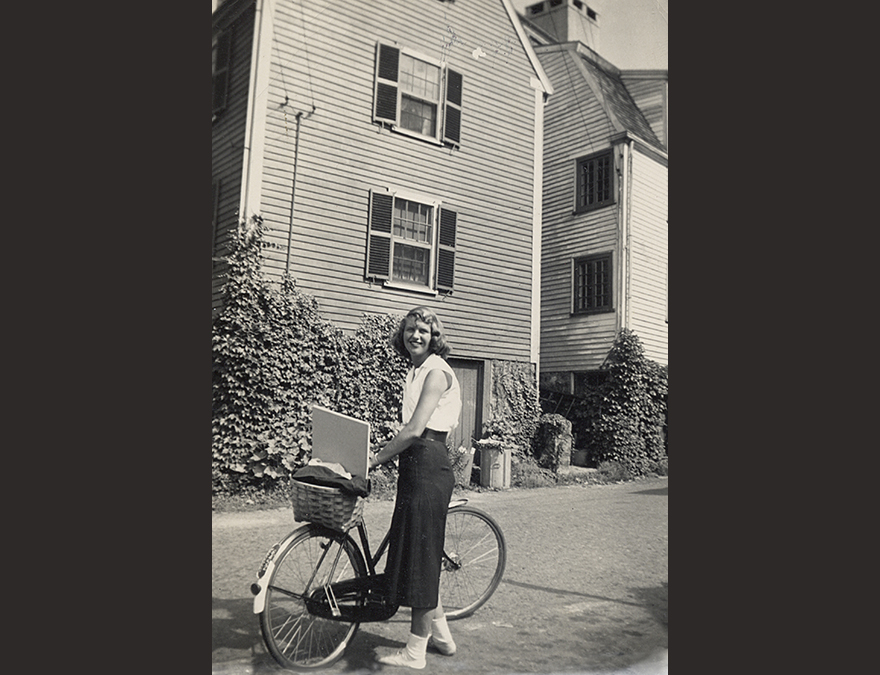 Young woman in the 1950s standing with her bike in front of a house.