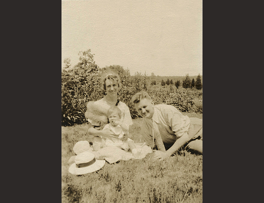 Photograph of a man and woman with a baby sitting on the grass