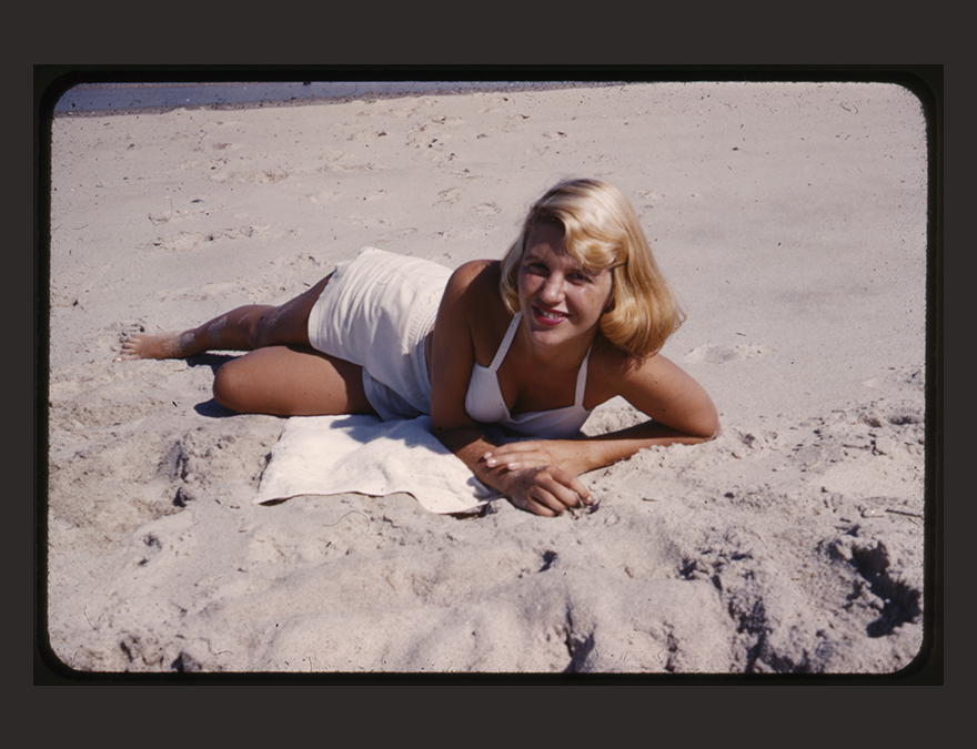 Woman in a white bathingsuit with blond hair lying on the beach