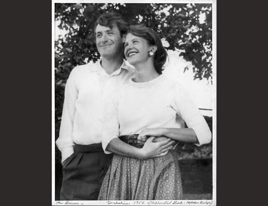 black and white photo of a young man and woman in white shirts his arm is around her waist.