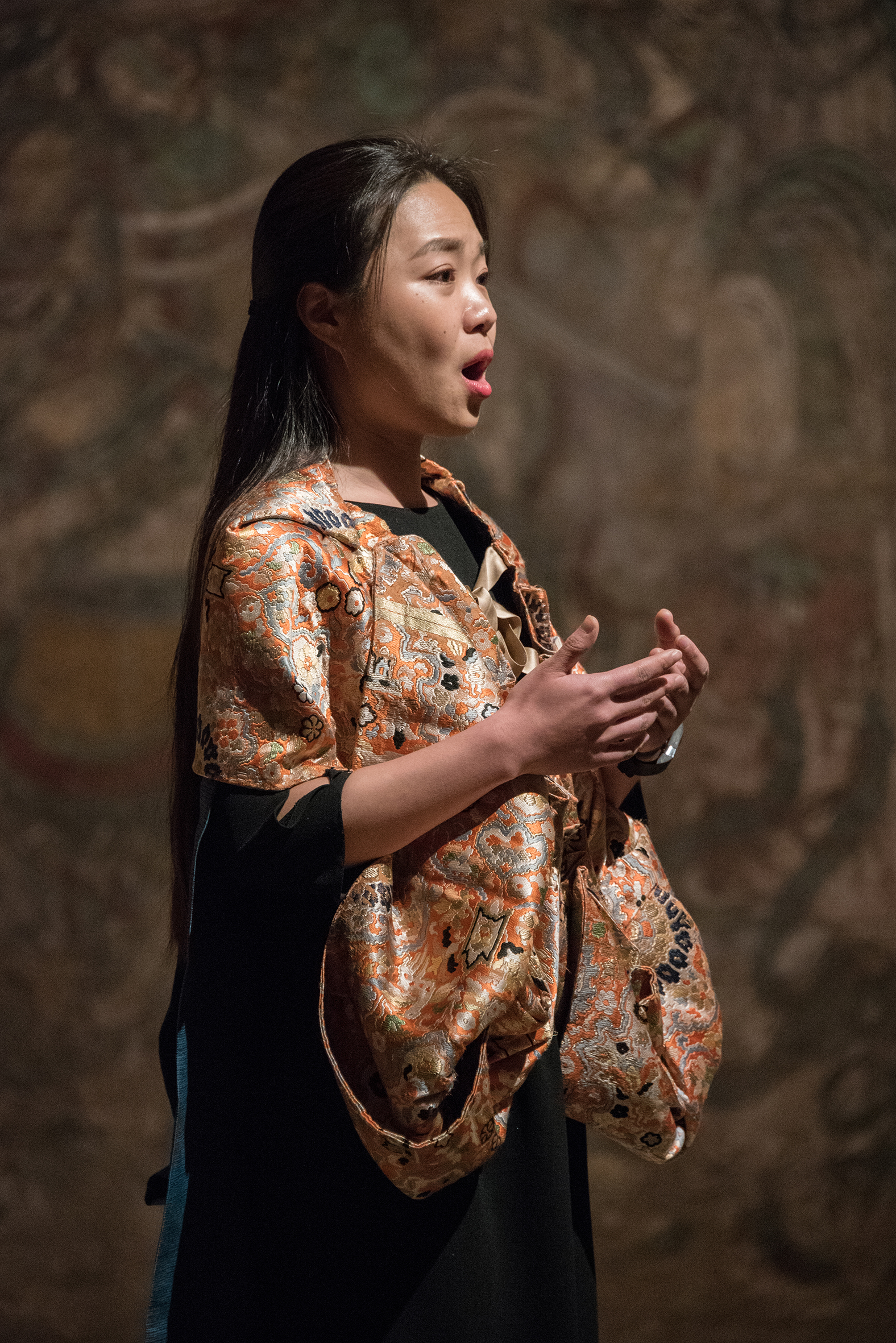 A photograph of a woman singing and wearing a beautiful robe
