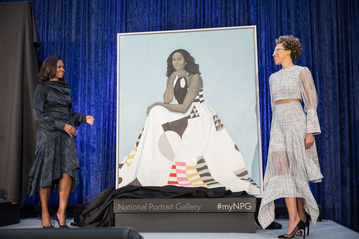 Two women standing on a stage next to a large portrait of a woman