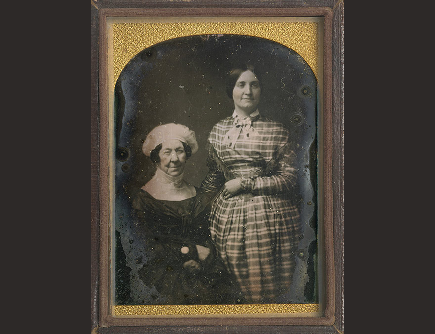 photograph of an older woman and a young woman standing behind her
