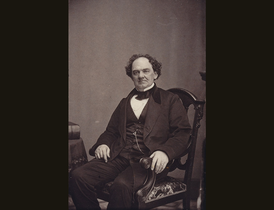 19th century man in a suit seated in a chair