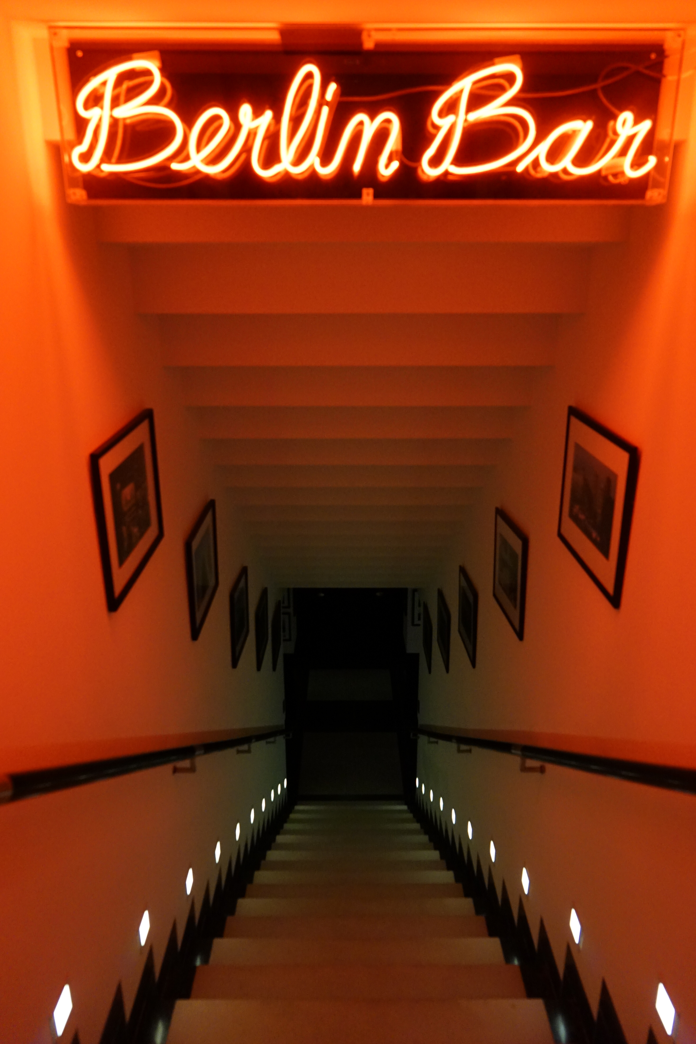 Image of a staircase with Berlin Bar in neon letters on the ceiling