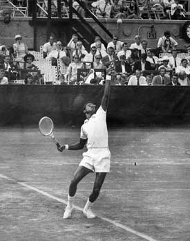 Black and white photo of Arthur Ashe. He is tossing the ball for his serve, at a tennis match