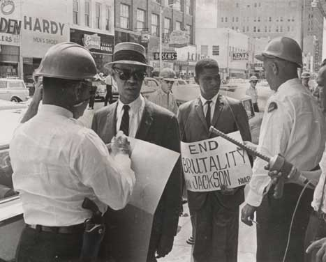 Black and white photo of Roy Wilkins and Medgar Evers, dressed in suits and being confronted by two police officers