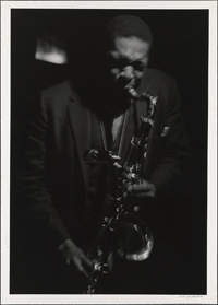 Black and white photo of John Coltrane playing saxophone