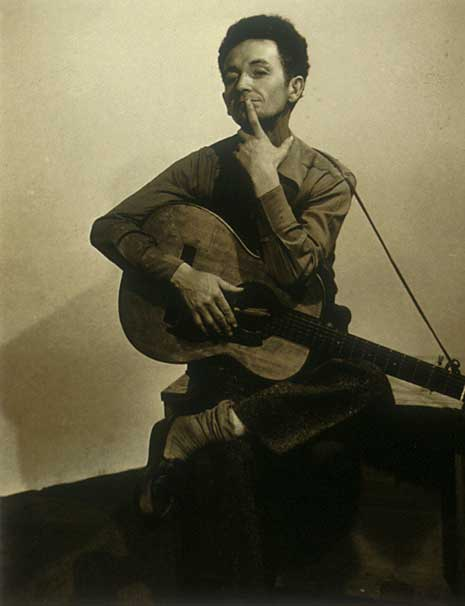 Sepia-toned photograph of Woody Guthrie with guitar