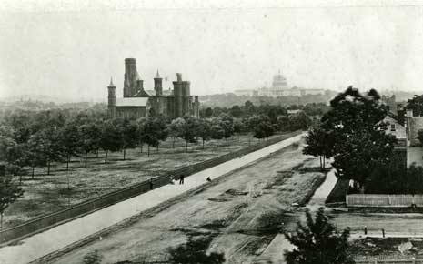 Black and white photo of the Smithsonian Castle at center left and the US Capitol in the center background.