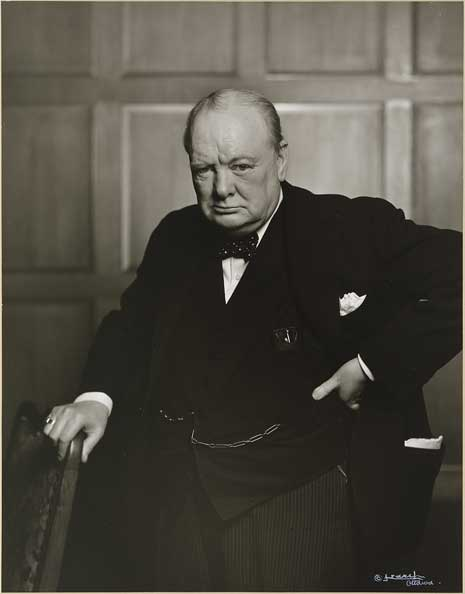Black and white photo of Sir Winston Churchill, waist up, in a black suit and bow tie, his right hand on a chair.