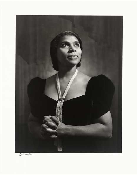 Black and white photo of Marian Anderson, in black dress, looking upwards, hands folded on each other