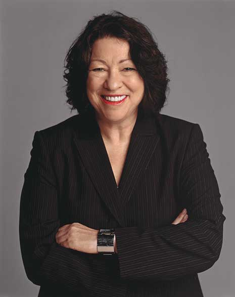 Sonia Sotomayor in black formal shirt and with arms crossed, looking straight into camera smiling