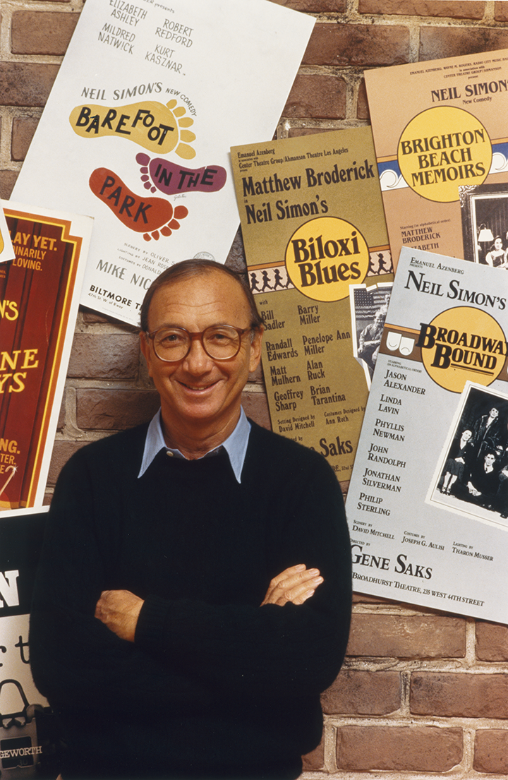 Man with round glasses against a wall of show posters