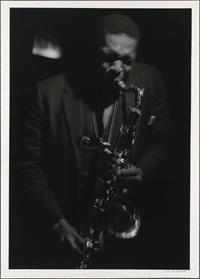 Black and white photo of John Coltrane playing saxophone