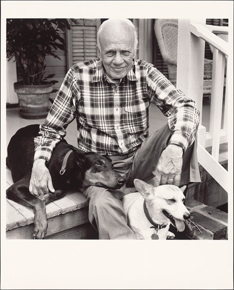 Black and white photo of Walker Percy on porch steps with two dogs