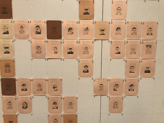 Photograph of drawings with flesh colored backgrounds tacked to a wall
