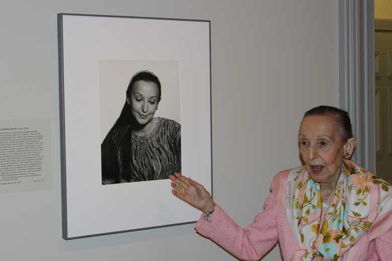 Estrellita Karsh, formally dressed, standing next to and gesturing toward a photo of herself on a wall.