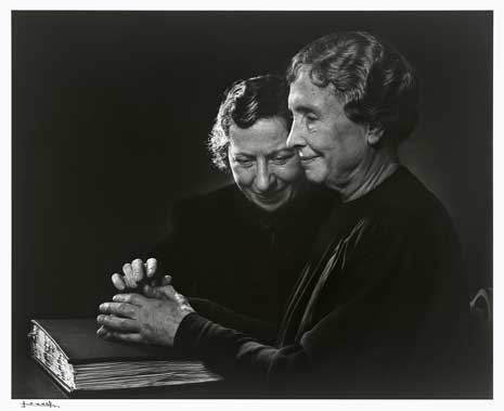 Black and white photo of Helen Keller and Polly Thompson seated at a table with a book.