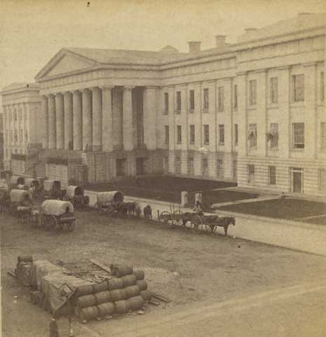 Black and white exterior photo of the US Patent Office Building, with horse-drawn carriages in the street.