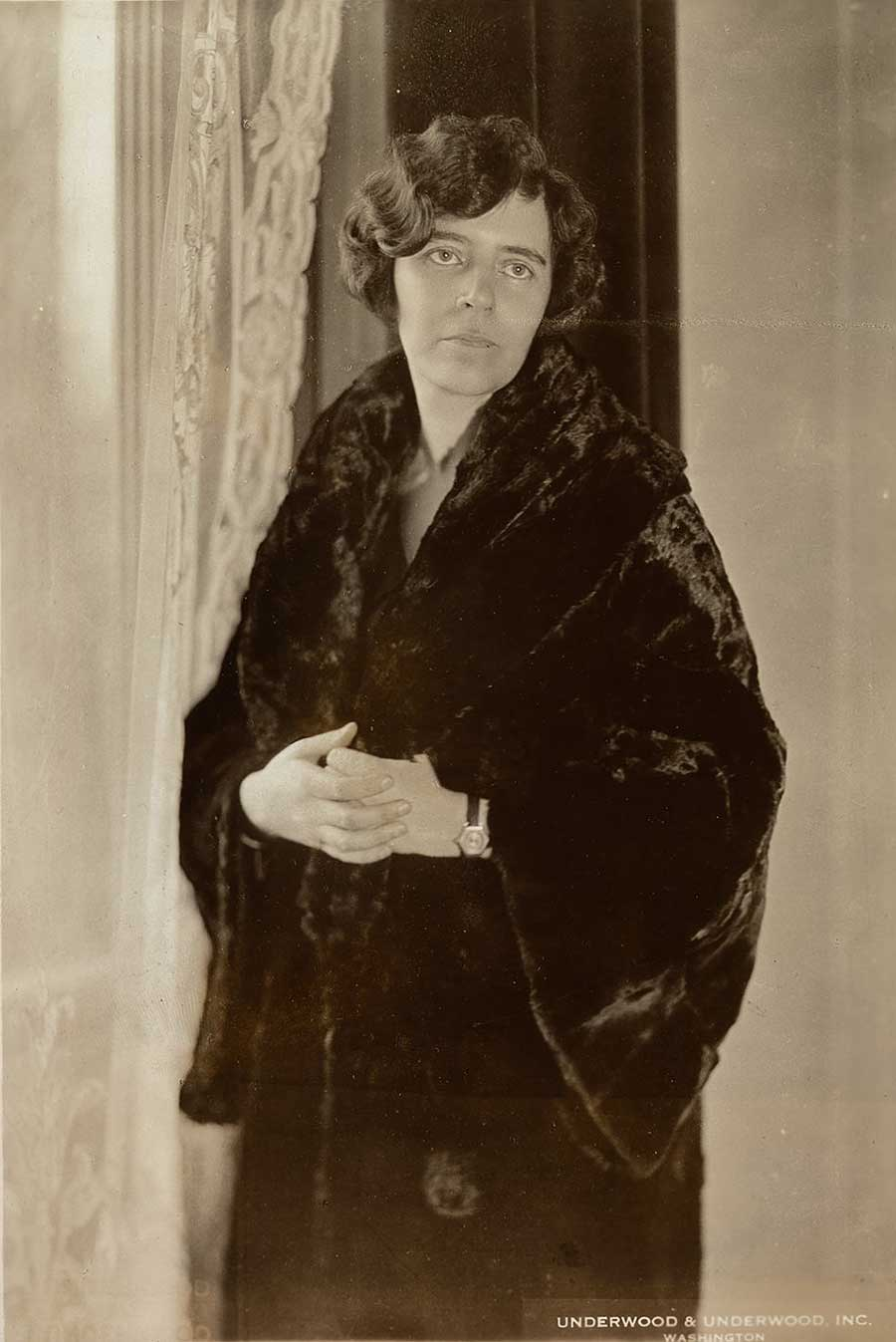 Sepia-toned photograph of Alice Paul standing in fur coat