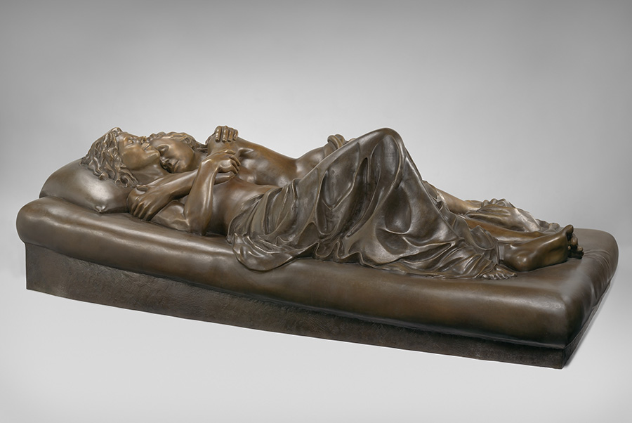 Bronze sculpture of two women on a bed, naked except for blanket in lover's embrace