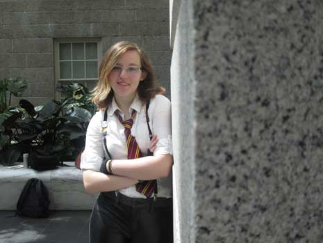 Kat McGrail in dress shirt, tie, and suspenders, with arms folded and looking at camera